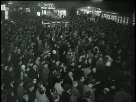 a large crowd in the main concourse of grand central station watches the friendship 7 launch on a large television screen - 1962 stock videos and b-roll footage