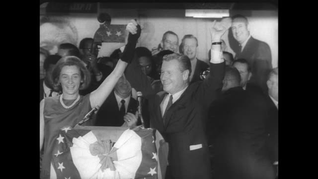 large crowd in the rockefeller campaign headquarters in new york after governor nelson rockefeller is reelected / sign reads 'rockefeller is... - ネルソン a ロッカフェラー点の映像素材/bロール