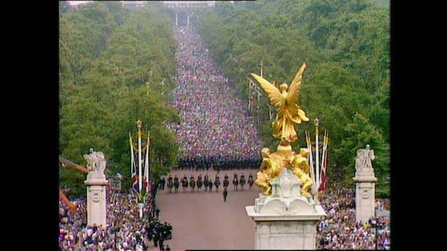 large crowd moves towards buckingham palace on the day of the wedding of prince charles and lady diana spencer; 1981. - crowd stock videos & royalty-free footage