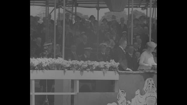 large crowd of british people wave small union jacks / queen mary is handed a dish of wine and she pours it on dock behind banner with heraldry /... - イングランド サウサンプトン点の映像素材/bロール