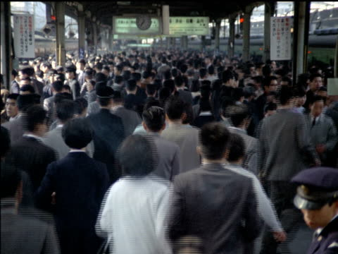 Large crowd of Japanese people walking away from camera / commuters moving though subway station towards camera Japanese commuters moving through...