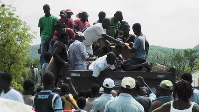 large crowd of people gather as food aid is distributed following devastating earthquake haiti; 12 march 2010 - number of people stock videos & royalty-free footage