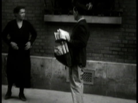 vidéos et rushes de large crowd of people near building woman talking w/ postman on sidewalk men talking at cafe table young adult male reading paper - 1934