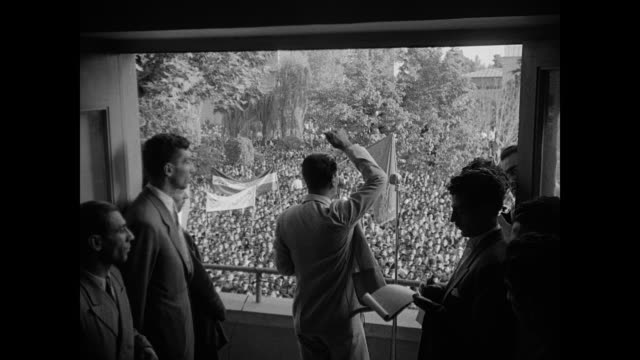 stockvideo's en b-roll-footage met large crowd of people outside some holding banners / unidentified iranian males on balcony speaking to crowd below crowd applauding / majlis of iran... - 1951
