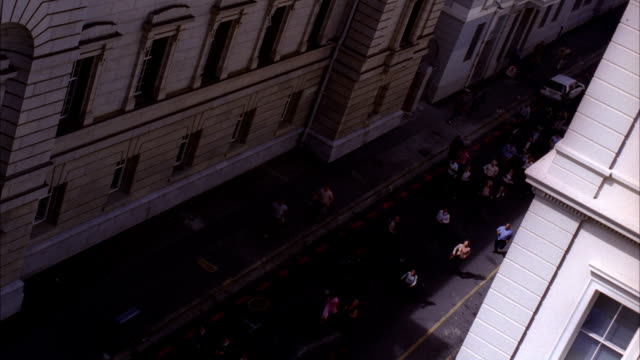 A large crowd of people run down a narrow city street. Available in HD.