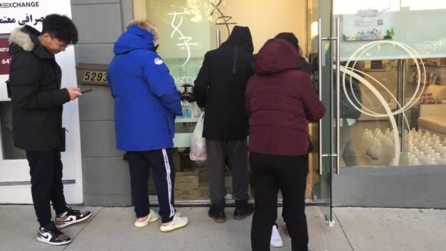 large crowd of people wearing face masks line up outside a shop selling industrial strength alcohol disinfectant, hand sanitizer, and n95 facemasks... - 洗剤点の映像素材/bロール