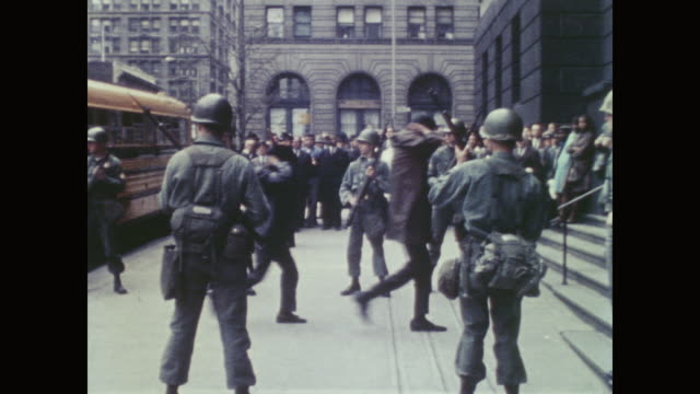 large crowd of police national guard citizens and onlookers watch as black prisoners depart school bus single file - prisoner walking stock videos & royalty-free footage