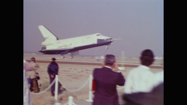 vídeos de stock e filmes b-roll de large crowd of press, staff and visitors line the runway as the enterprise space shuttle comes into land. enterprise is taxied away on the back of a... - 1977