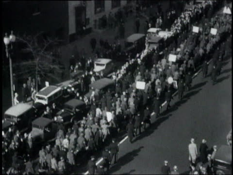 WS large crowd of protesters marching along street beside parked cars / United States