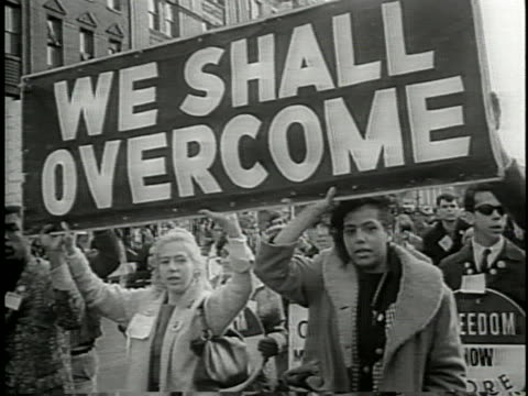 "vídeos de stock, filmes e b-roll de large crowd of protestors walking from selma to montgomery for equal voting rights for african americans, holding a sign ""we shall overcome"". - 1965"