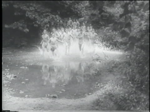 b/w 1943 large crowd of shirtless men running thru puddle on dirt path / us navy cadets - shirtless stock videos & royalty-free footage