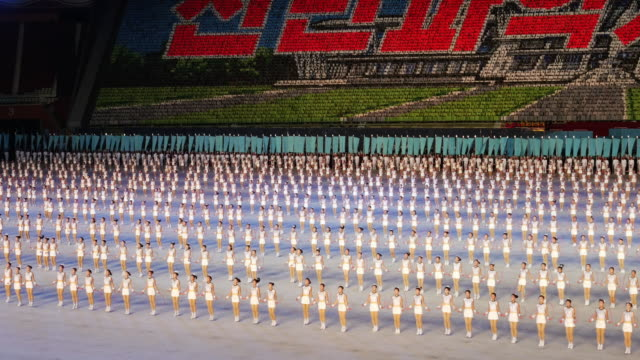 large crowd of synchronised rope-juming girls dancers performing a beautiful synchronized ballet formation during mass games in pyongyang, north korea, dprk. medium wide shot - north korea stock videos & royalty-free footage