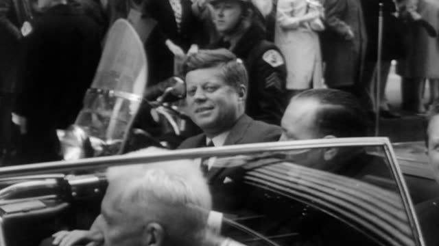 large crowd outside the airport / president kennedy and assorted dignitaries walk towards a large stone memorial / girl scouts watch from the crowd /... - back to front stock videos and b-roll footage