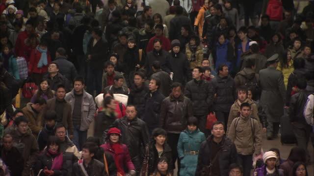 vidéos et rushes de a large crowd passes through beijing west railway station. - pékin