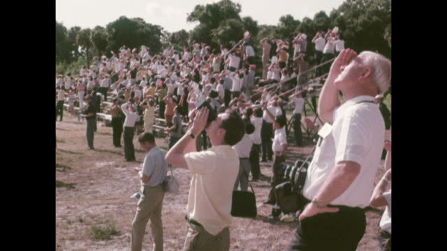 vídeos de stock e filmes b-roll de large crowds gather to watch the launch of apollo 11, which is due to land on the moon from the kennedy space center in florida. sp00251 ss rt: 7:57... - prt