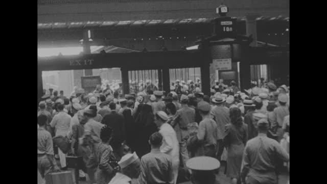vídeos y material grabado en eventos de stock de vs large crowds of american service people and civilians bustling though train station / people at large ticket counter / note exact day not known - estación de tren