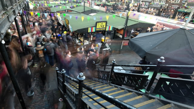 large crowds of people queue for a lunch time snack at one of the many street food stalls in camden lock market - booth stock videos & royalty-free footage