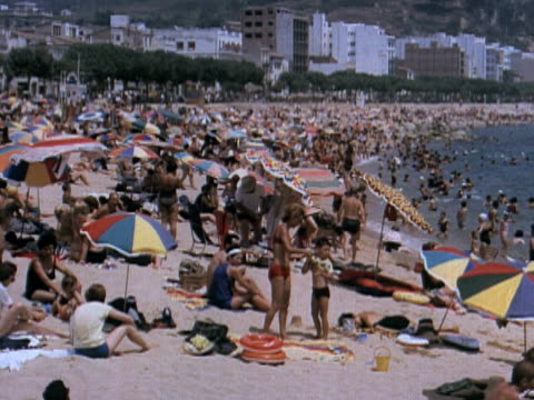 1960 MONTAGE large crowds of people relaxing on beach / Spain
