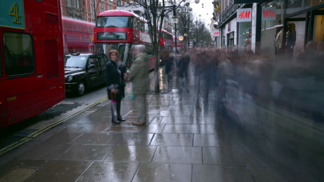large crowds of people shopping rapidly travel along oxford street taking advantage of the january sales on a wet wintry day - oxford street stock-videos und b-roll-filmmaterial