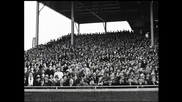 vídeos y material grabado en eventos de stock de large crowds watching football game inside stadium, crowd forming patterns; football players running in the field and crowds standing up and cheering - 1940 1949