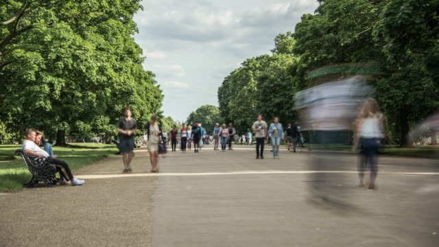 vidéos et rushes de large crowns of tourists move along the broad walk as they enjoy a warms summers day in hyde park - banc public