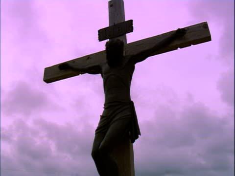 vídeos de stock, filmes e b-roll de large crucifix against a pink sky - figura masculina