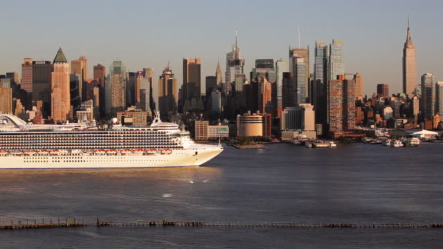 a large cruise ship moves along the hudson river past the manhattan skyline. - cruise ship stock videos & royalty-free footage