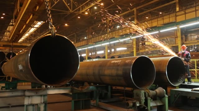 large diameter steel pipes move along the production line before welding at the izhora pipe mill operated by severstal pjsc in the kolpino district... - pipe tube stock videos and b-roll footage