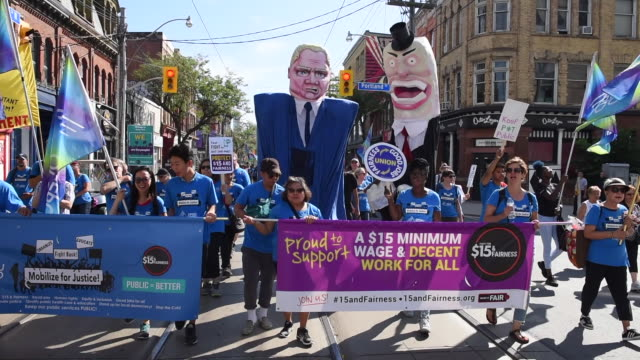 Large doll or toy representing Doug Ford Premier of Ontario for the Conservative Party accompanied by workers demands The Toronto Labor Day Parade is...