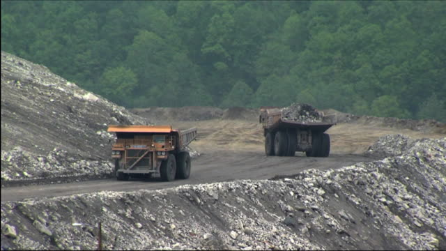 WS large dump trucks moving earth at open pit coal mine / Bob White, West Virginia