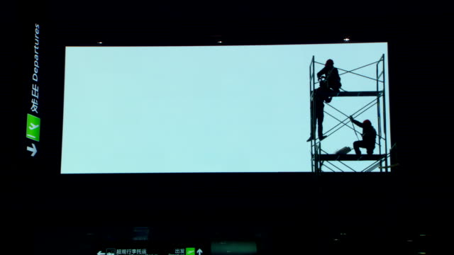 a large electronic billboard silhouettes workers on scaffolding. - scaffolding stock videos & royalty-free footage