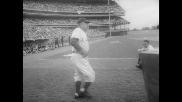 large evening crowd in shea stadium / casey stengel on the field applauding / crowd stands and begin to applaud / stengel walks up to large birthday... - チーム写真点の映像素材/bロール