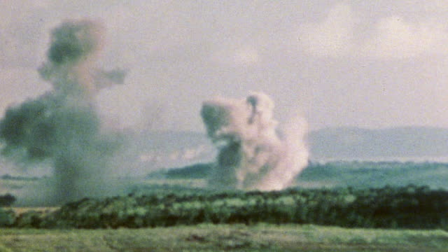 vídeos y material grabado en eventos de stock de large explosive plumes of smoke rising and us marines observing the shelling during wwii / tinian mariana islands¬† - tinian