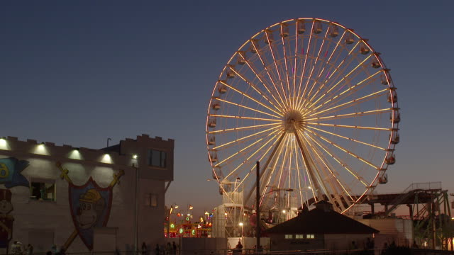a large ferris wheel spins at an amusement park on the jersey shore. it is twilight and the ferris wheel is lit up.  you see the side of gillian's wonderland pier in ocean city. - 遊歩道点の映像素材/bロール