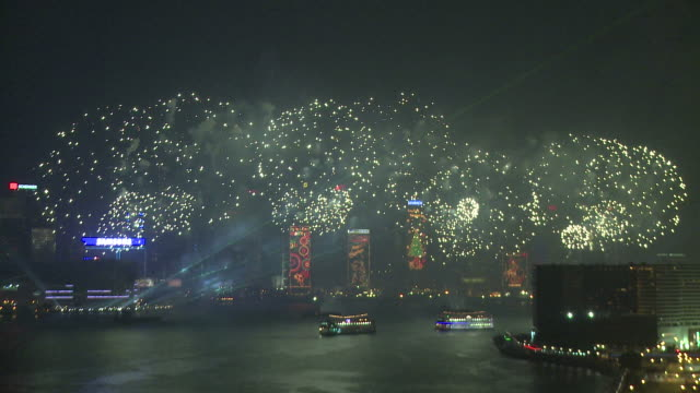 vidéos et rushes de large fireworks and sparks rain down over hong kong's victoria harbour, from tsim sha tsui, kowloon, east asian games opening ceremony fireworks display, december 2009 - cérémonie