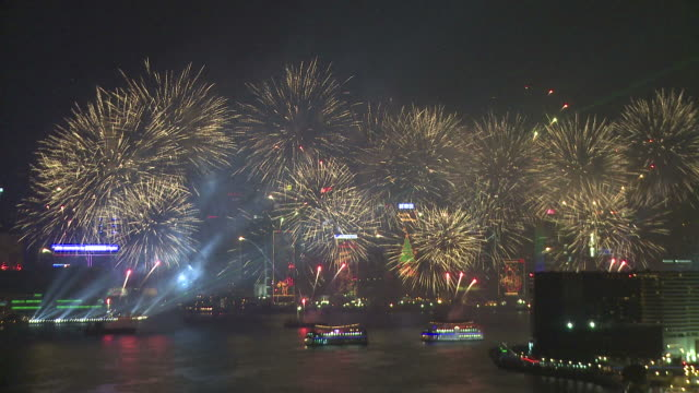 Large fireworks and sparks rain down over Hong Kong's Victoria Harbour, from Tsim Sha Tsui, Kowloon, East Asian Games Opening Ceremony Fireworks Display, December 2009