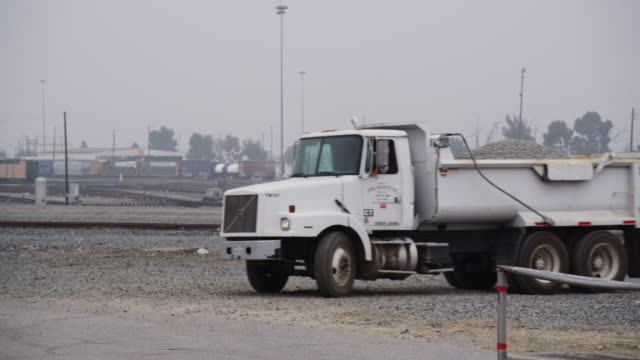 a large forklift and dump truck with gravel drive through a busy freight train yard construction site. - dump truck stock videos and b-roll footage
