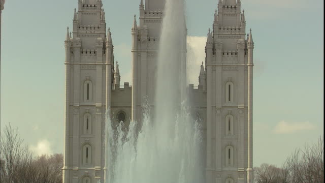 A large fountain sprays water in front of the temple of The Church of Jesus Christ of Latter-Day Saints in Salt Lake City.