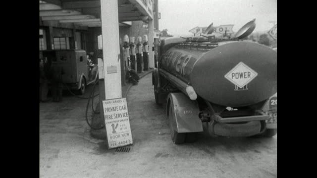 a large fuel tanker delivers fuel to a petrol station; 1950 - cap stock videos & royalty-free footage
