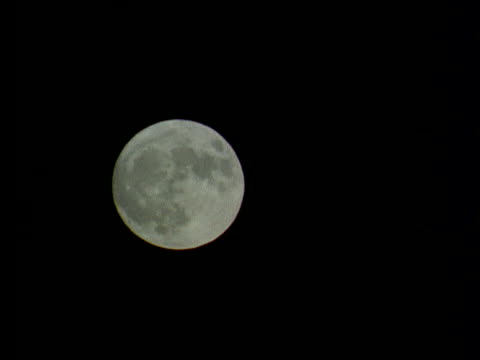 stockvideo's en b-roll-footage met large full moon moves across sky - oneindigheid