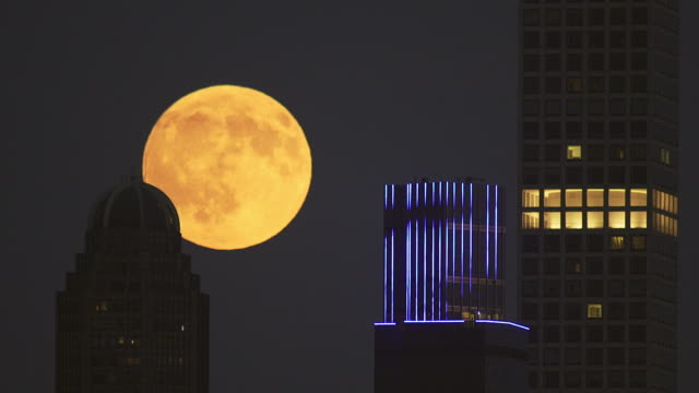 Large full moon rises behind NYC buildings