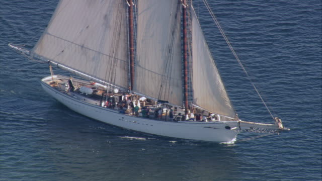 AERIAL Large gaff-rigged schooner yacht leaving the calm blue waters of the harbor / New Bedford, Massachusetts, United States