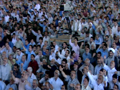 large gathering of worshipers seated for midday prayer / qom, iran - credente video stock e b–roll