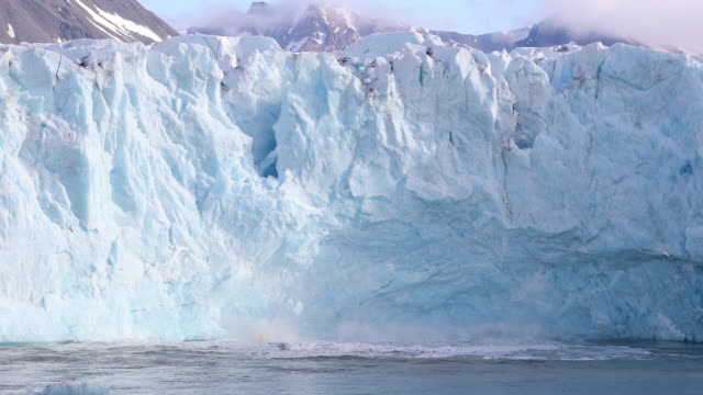 large glacier calving in svalbard at monacobreen - ghiacciato video stock e b–roll