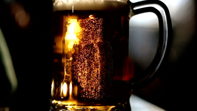 large glass mug with fresh beer on a table in pub - beer glass stock videos & royalty-free footage