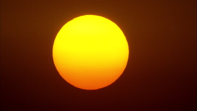 Large golden sun gradually sets, Maui, Available in HD.