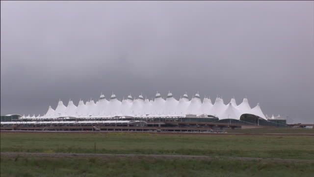 stockvideo's en b-roll-footage met a large green field stretches towards denver international airport. - dia