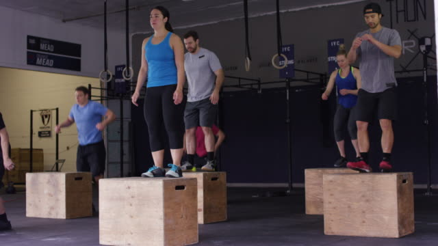 Large group class doing box jumps together in an industrial gym