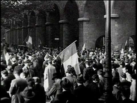 vidéos et rushes de large group march in paris carrying a french communist party banner / people gather in the streets waving french flags in the air / people run... - 1934