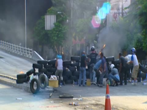 large group of anti-government protesters gathered on street following violent clashes with armed government forces thailand; 15 may 2010 - violence stock videos & royalty-free footage